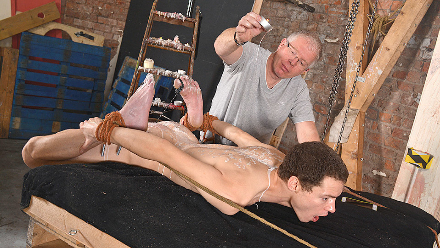Jonny is in a very tricky position, roped down with his hard cock throbbing  and his arse on show, no wonder master Sebastian is making full use of him!